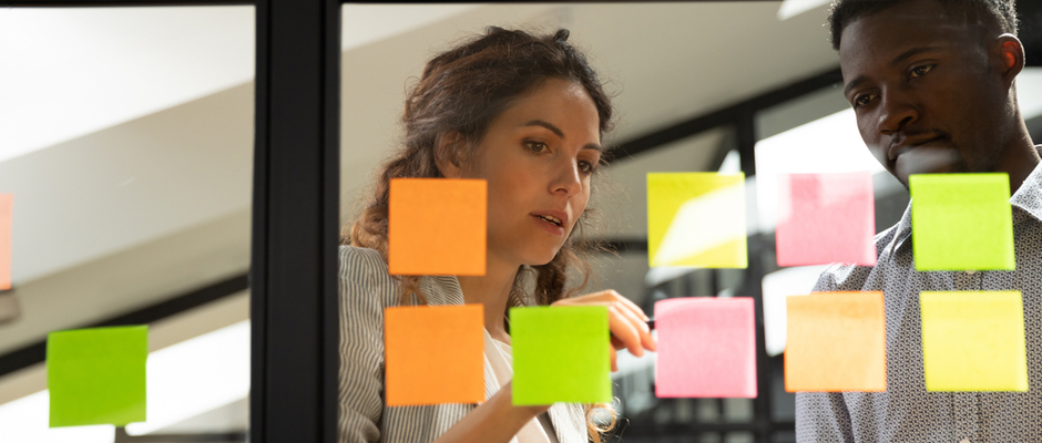 image of woman and man looking at sticky notes on a board to represent trying something different
