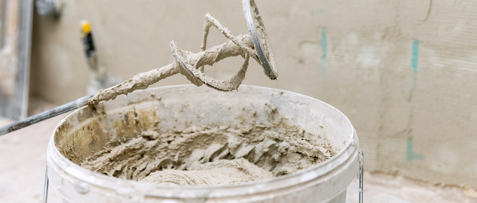 image of tool used to mix cement for stucco with bucket of wet cement