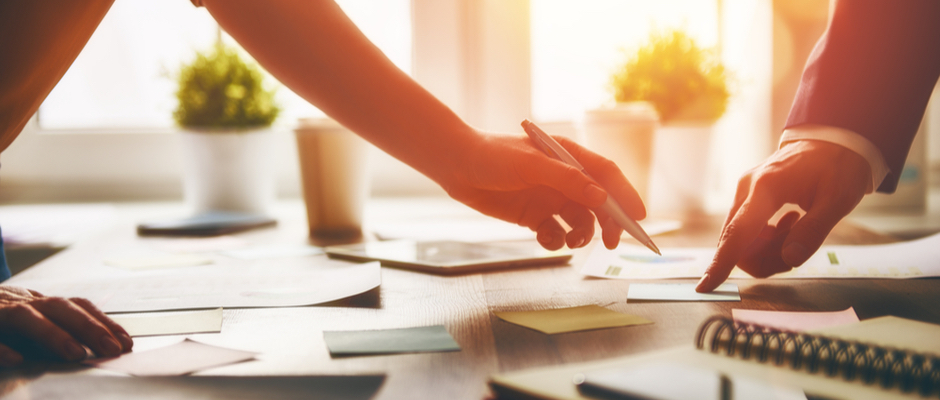 image of hands working with paperwork on a desk