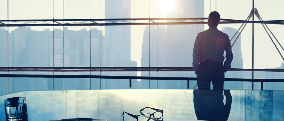 image of white collar businessman looking out a high rise office building window